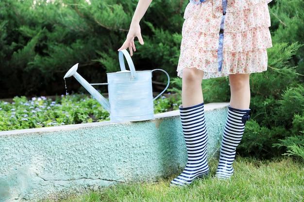 Mulher jovem com botas de borracha segurando um regador, ao ar livre