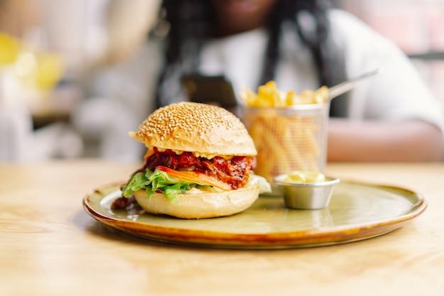 Mulher jovem com cabelo afro comendo um hambúrguer clássico saboroso com batatas fritas