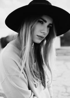 Mulher jovem com cabelo comprido e um grande chapéu preto