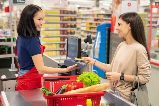 Mulher jovem com cabelo comprido em frente ao caixa pagando por produtos em um supermercado moderno com cartão do banco