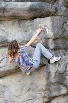Mulher jovem com cabelo comprido pendurado na face rochosa de uma montanha enquanto escala sem apoio de corda