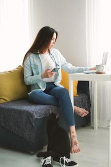 Mulher jovem com cabelo comprido se senta no sofá em casa e trabalha em smartphone