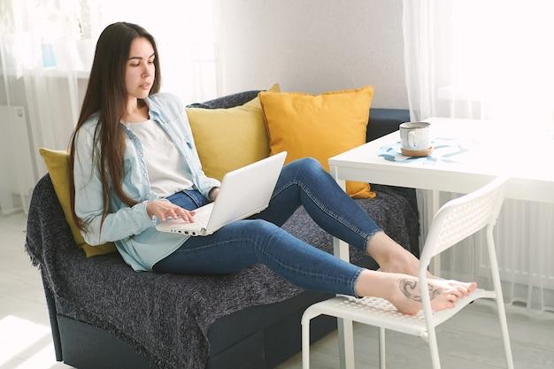 Mulher jovem com cabelo comprido sentada no sofá em casa a trabalhar no portátil
