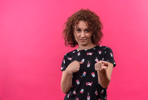 Mulher jovem com cabelo curto e encaracolado com expressão cética a apontar os dedos para si mesma e para a frente