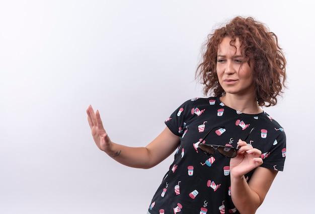 Mulher jovem com cabelo curto e encaracolado com os braços estendidos, fazendo gesto de defesa enquanto dizendo não se aproxime de pé sobre uma parede branca