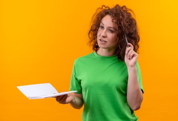 Mulher jovem com cabelo curto e encaracolado com uma camiseta verde segurando um caderno e uma caneta olhando para o lado com uma expressão pensativa no rosto em pé