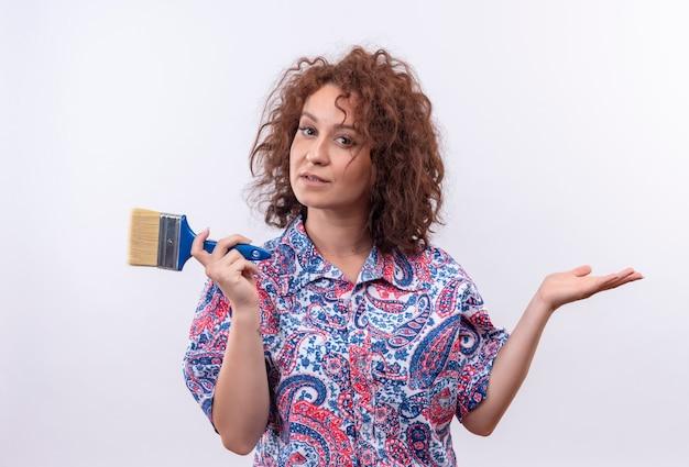Mulher jovem com cabelo curto e encaracolado em uma camisa colorida segurando um pincel, sorrindo, apresentando-se com o braço da mão em pé sobre uma parede branca