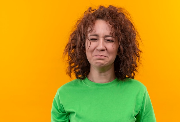 Mulher jovem com cabelo curto e encaracolado em uma camiseta verde chorando com uma cara infeliz em pé sobre uma parede laranja
