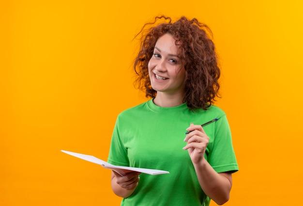 Mulher jovem com cabelo curto e encaracolado em uma camiseta verde segurando um caderno e uma caneta sorrindo, positiva e feliz em pé