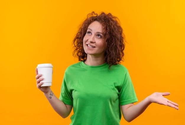 Mulher jovem com cabelo curto e encaracolado em uma camiseta verde segurando uma xícara de café, olhando para cima, sorrindo e estendendo o braço para o lado em pé sobre uma parede laranja