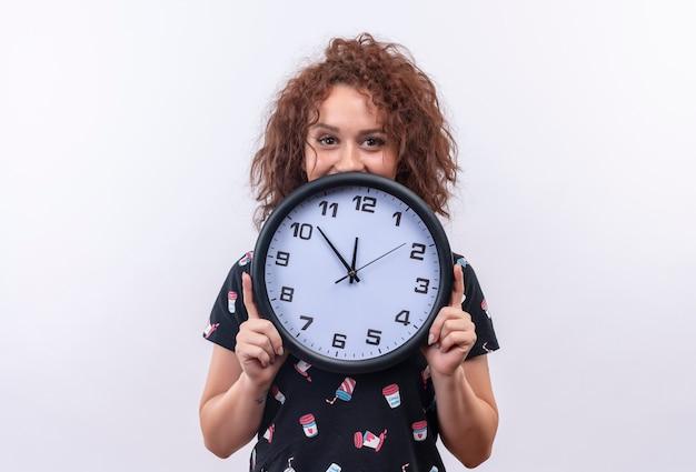 Mulher jovem com cabelo curto e encaracolado segurando um relógio de parede feliz e sorrindo em pé sobre uma parede branca