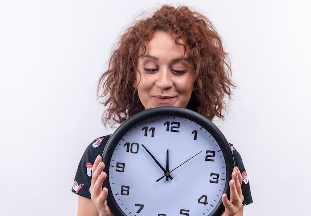 Mulher jovem com cabelo curto e encaracolado segurando um relógio de parede olhando para ele com emoções positivas em pé sobre uma parede branca