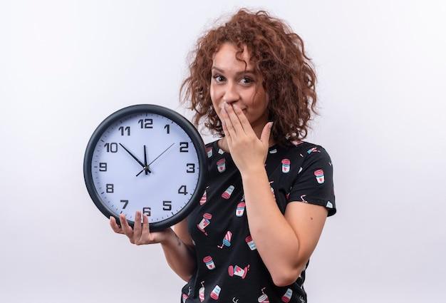 Mulher jovem com cabelo curto e encaracolado segurando um relógio de parede parecendo surpresa, cobrindo a boca com a mão em pé sobre uma parede branca