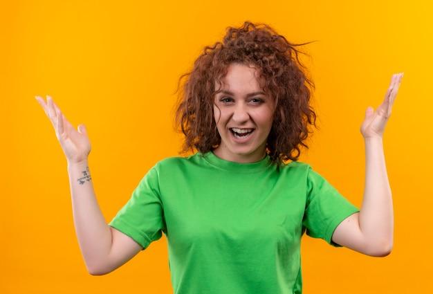 Mulher jovem com cabelo curto e encaracolado usando uma camiseta verde parecendo surpresa e empolgada com os braços levantados em pé
