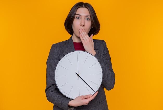 Mulher jovem com cabelo curto e jaqueta cinza segurando um relógio de parede