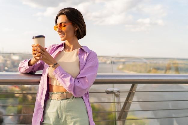 Mulher jovem com cabelo curto e roupa chique de verão bebe café na ponte moderna