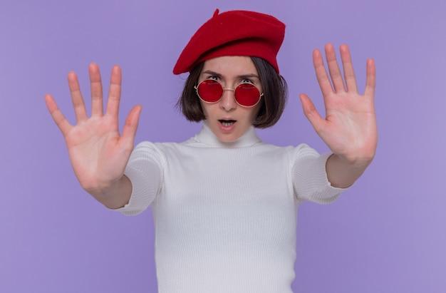 Mulher jovem com cabelo curto em gola alta, boina e óculos de sol vermelhos, olhando para a frente com uma cara séria, fazendo gesto de pare com as mãos em pé sobre a parede azul