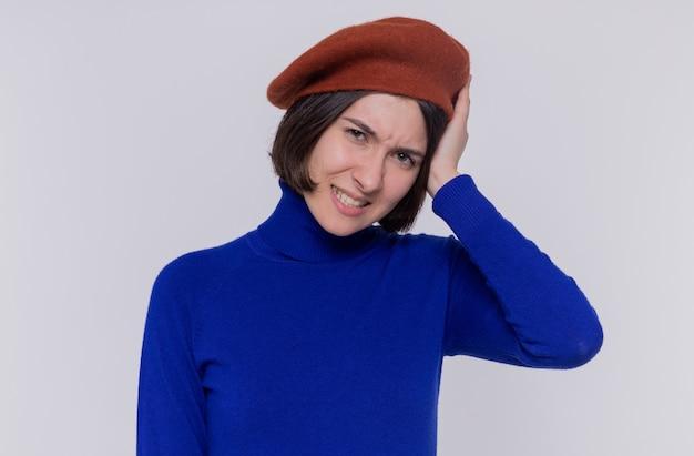 Mulher jovem com cabelo curto em gola olímpica azul e boina, olhando para a frente, confusa, segurando a cabeça por engano ao pisar na parede branca