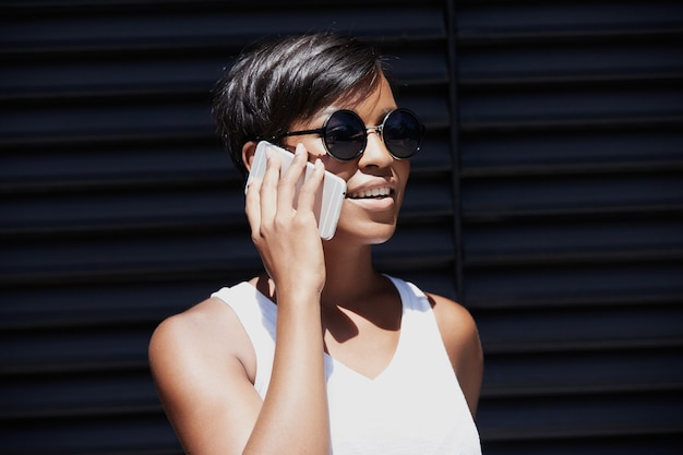 Mulher jovem com cabelo curto falando ao telefone