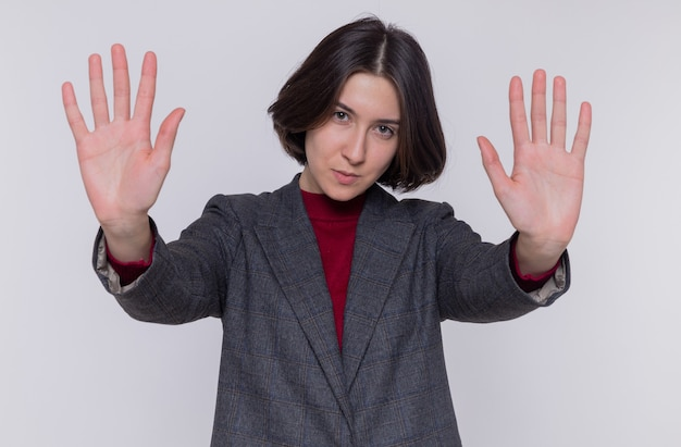 Mulher jovem com cabelo curto, vestindo uma jaqueta cinza, olhando para a frente com uma cara séria, fazendo gesto de pare com as mãos em pé sobre uma parede branca