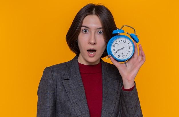 Mulher jovem com cabelo curto, vestindo uma jaqueta cinza, segurando um despertador, olhando para a frente espantada e surpresa em pé sobre a parede laranja