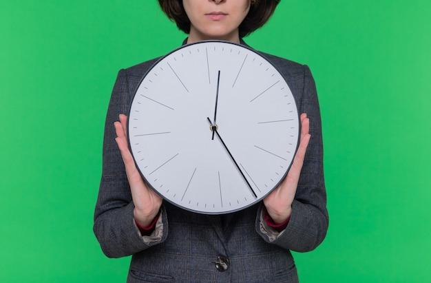 Mulher jovem com cabelo curto, vestindo uma jaqueta cinza, segurando um relógio de parede, parecendo confiante em pé sobre a parede verde