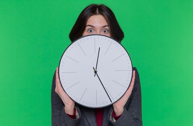 Mulher jovem com cabelo curto, vestindo uma jaqueta cinza, segurando um relógio de parede, parecendo espantada e surpresa em pé sobre a parede verde