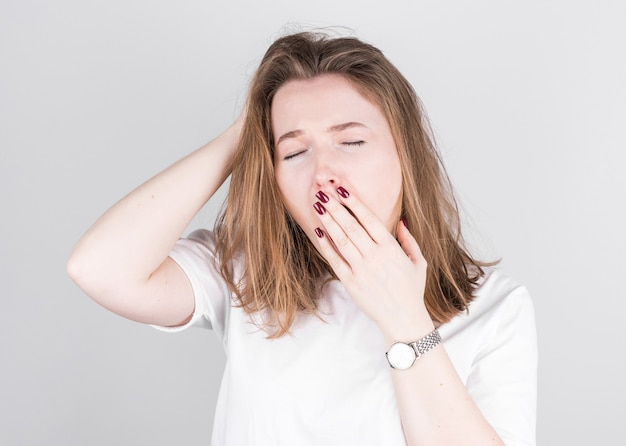 Mulher jovem com cabelo desgrenhado bocejando de cansaço contra uma parede cinza