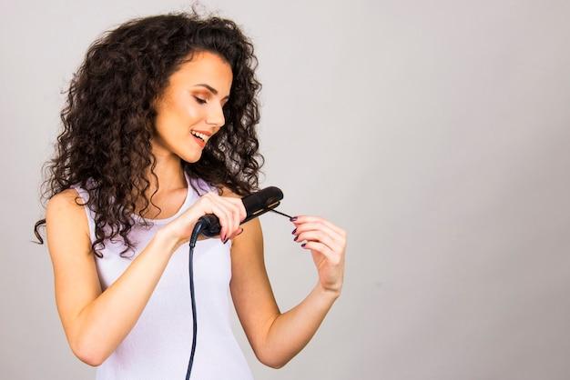 Mulher jovem com cabelo encaracolado e alisador de cabelo