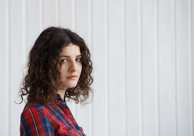 Mulher jovem com cabelo encaracolado e camisa xadrez