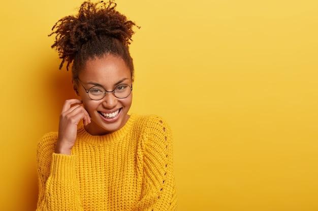 Mulher jovem com cabelo encaracolado e camisola amarela