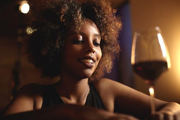 Mulher jovem com cabelo encaracolado e um copo de vinho tinto