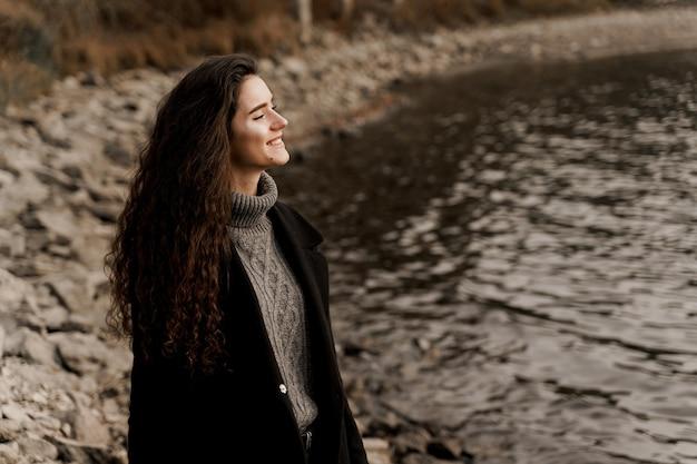Mulher jovem com cabelo encaracolado em pé junto ao lago