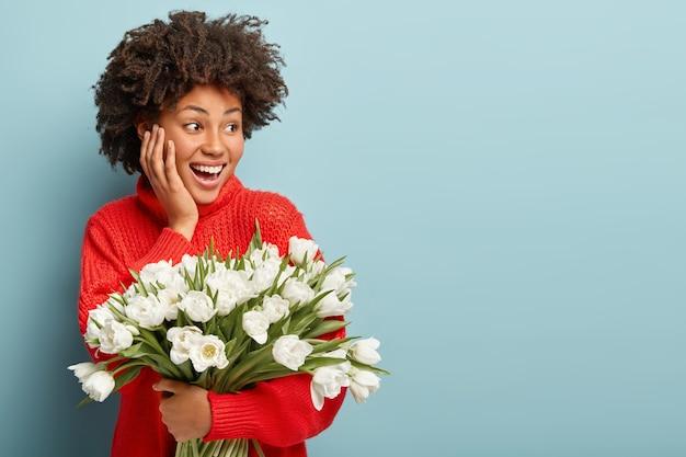 Mulher jovem com cabelo encaracolado segurando um buquê de flores brancas