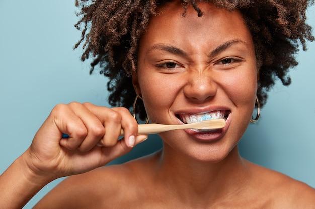 Mulher jovem com cabelo encaracolado segurando uma escova de dentes