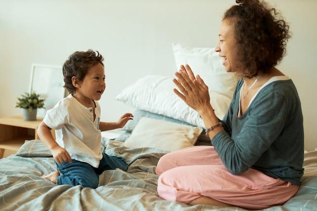 Mulher jovem com cabelo encaracolado sentada na cama com um filho adorável