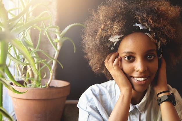 Mulher jovem com cabelo encaracolado sentada num café