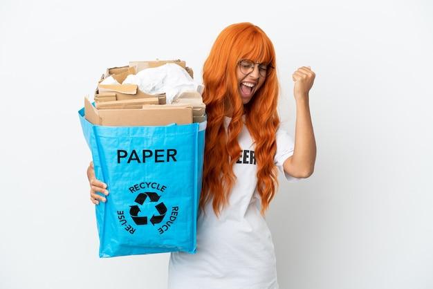 Mulher jovem com cabelo laranja segurando uma sacola cheia de papel para reciclar isolado no fundo branco comemorando uma vitória