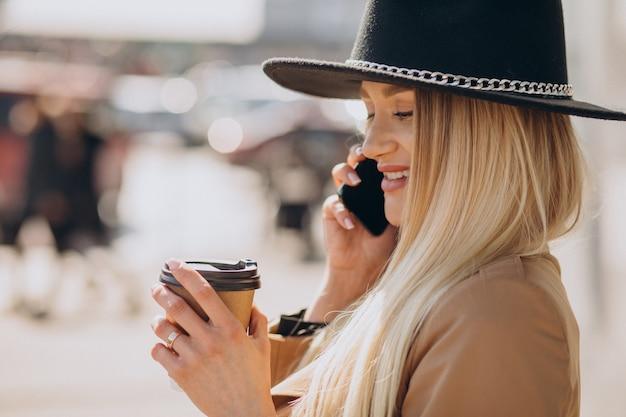 Mulher jovem com cabelo loiro e chapéu preto falando ao telefone e bebendo café