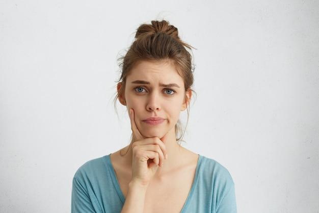 Mulher jovem com cabelo loiro e olhos azuis, franzindo a testa, segurando o dedo indicador no queixo, tendo dúvidas e suspeitas, sentindo-se cética sobre algo. conceito de emoções e expressões humanas