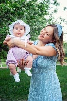 Mulher jovem com cabelo loiro solto balança nos braços da menina e brinca com a criança em pé no parque contra árvores verdes em flor branca