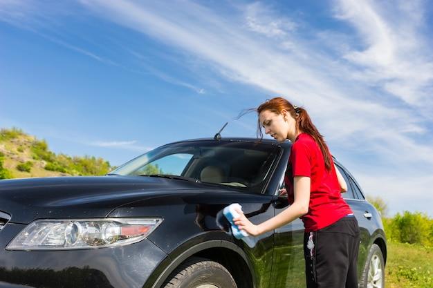 Mulher jovem com cabelo longo castanho-avermelhado e camisa vermelha, lavando um veículo preto de luxo com esponja em campo verde em dia ensolarado
