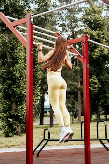 Mulher jovem com cabelo longo e reto fazendo exercícios de rua levanta-se em uma barra na quadra de esportes no parque, vista traseira