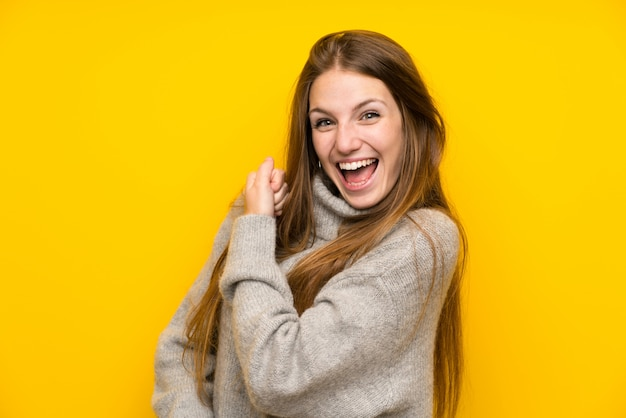 Mulher jovem, com, cabelo longo, sobre, amarela, celebrando, um, vitória