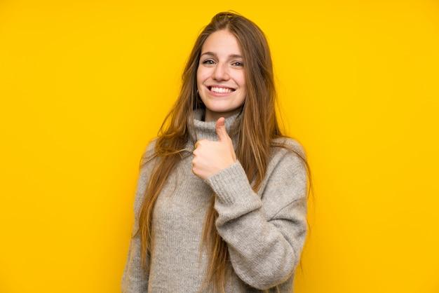 Mulher jovem, com, cabelo longo, sobre, amarela, dar, um, polegares cima, gesto