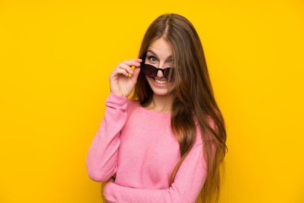 Mulher jovem, com, cabelo longo, sobre, isolado, parede amarela, com, óculos, e, sorrindo