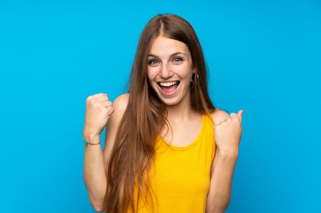 Mulher jovem, com, cabelo longo, sobre, isolado, parede azul, celebrando, um, vitória, em, vencedor, posição