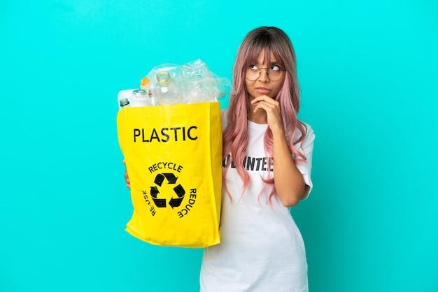 Mulher jovem com cabelo rosa segurando uma sacola cheia de garrafas plásticas para reciclar isolada em um fundo azul, tendo dúvidas e pensando