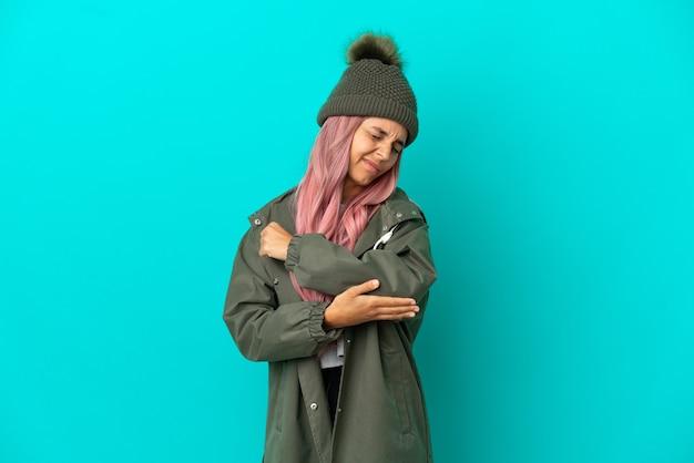 Mulher jovem com cabelo rosa vestindo um casaco à prova de chuva isolado em um fundo azul com dor no cotovelo