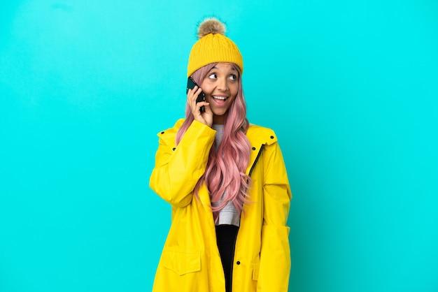 Mulher jovem com cabelo rosa vestindo um casaco à prova de chuva isolado em um fundo azul, conversando com o telefone celular